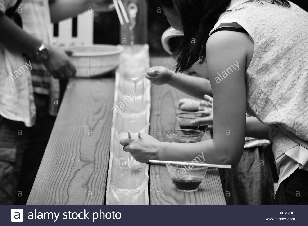 Midsection Of People Having Somen In Restaurant - Stock Image