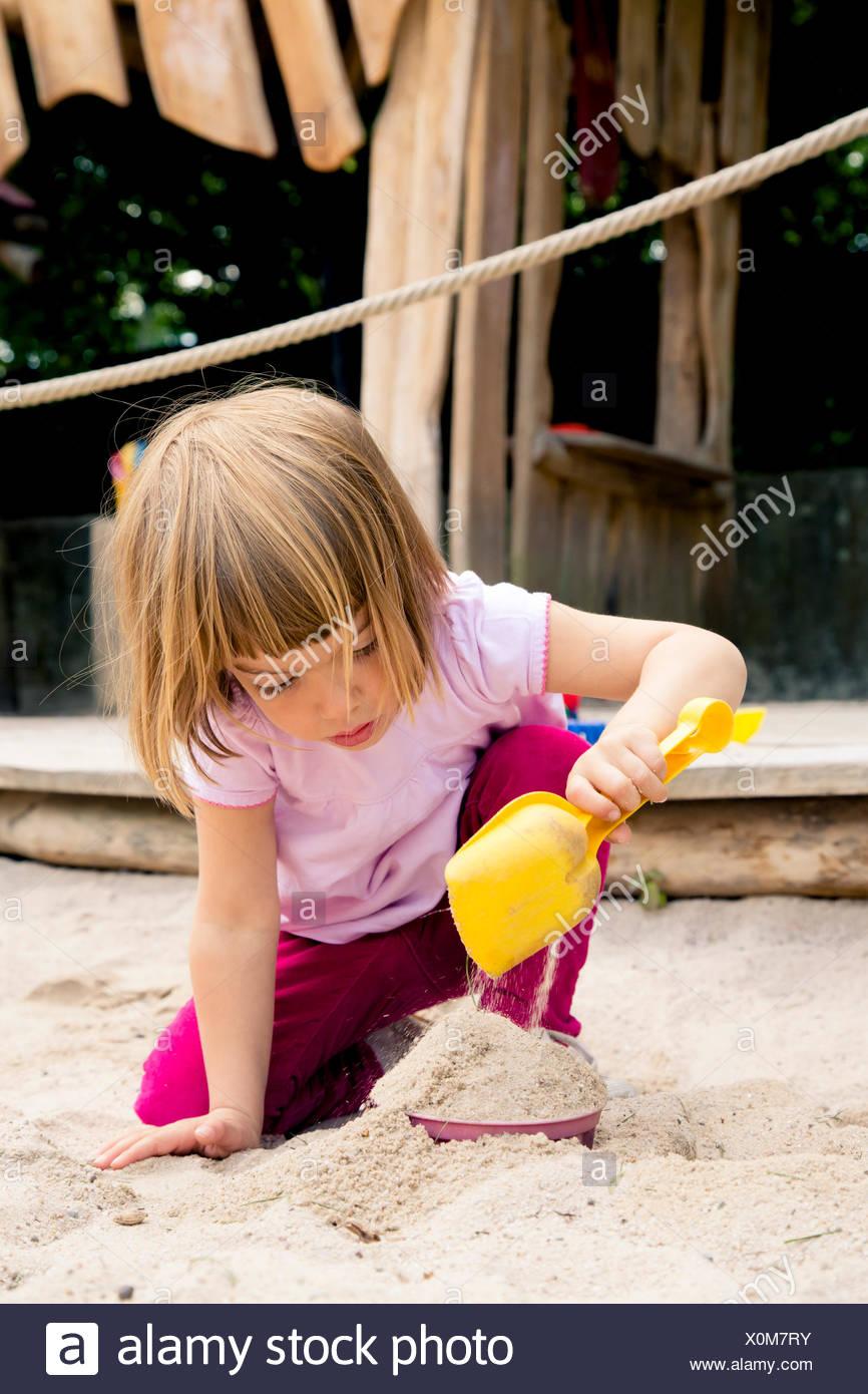 Little girl on playground balancing in sandbox - Stock Image