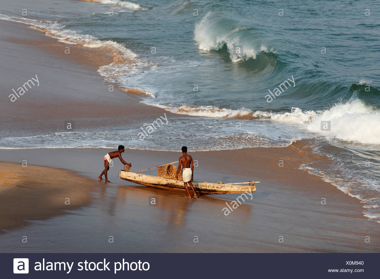 Two locals with a simple fishing boat on a beach south of Kovalam, Malabar Coast, Malabar, Kerala, southern India, India, Asia - Stock Image