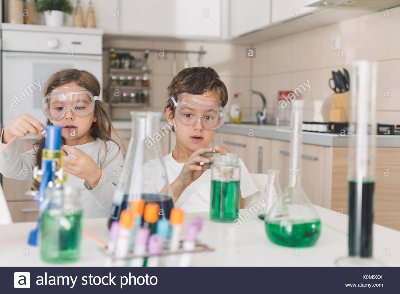 Boy and girl playing science experiments at home Stock Photo