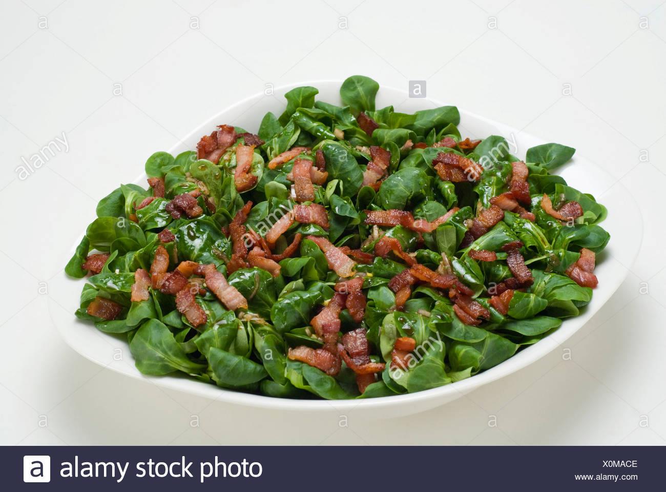 Field salad (Valerianella locusta) with roasted bacon strips Stock Photo