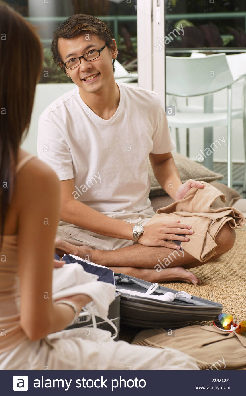 Couple at home, sitting at home, folding clothes - Stock Image