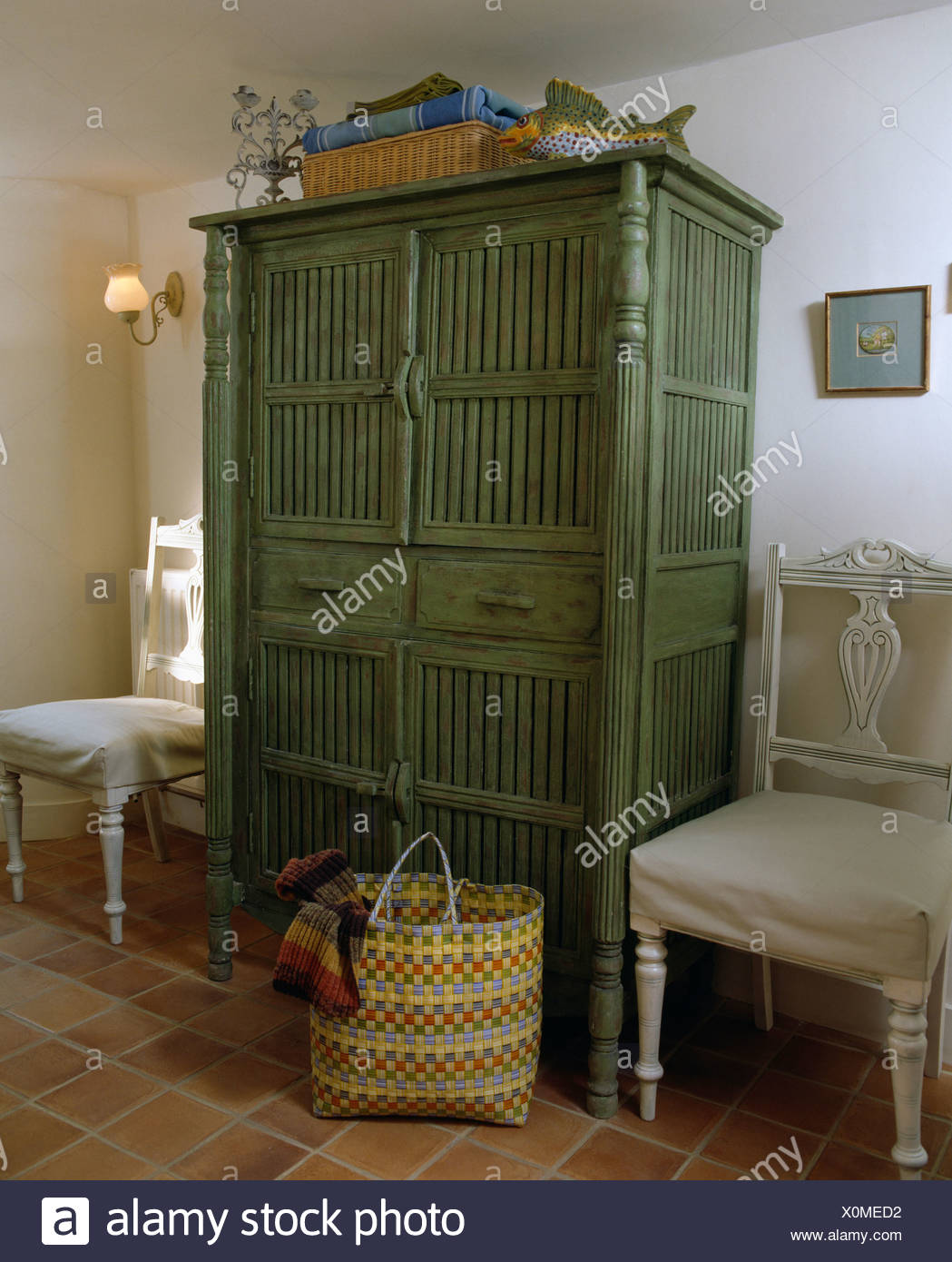 White Painted Chairs With Linen Loose Covers On Either Side Of Green Cupboard In Cottage Dining Room