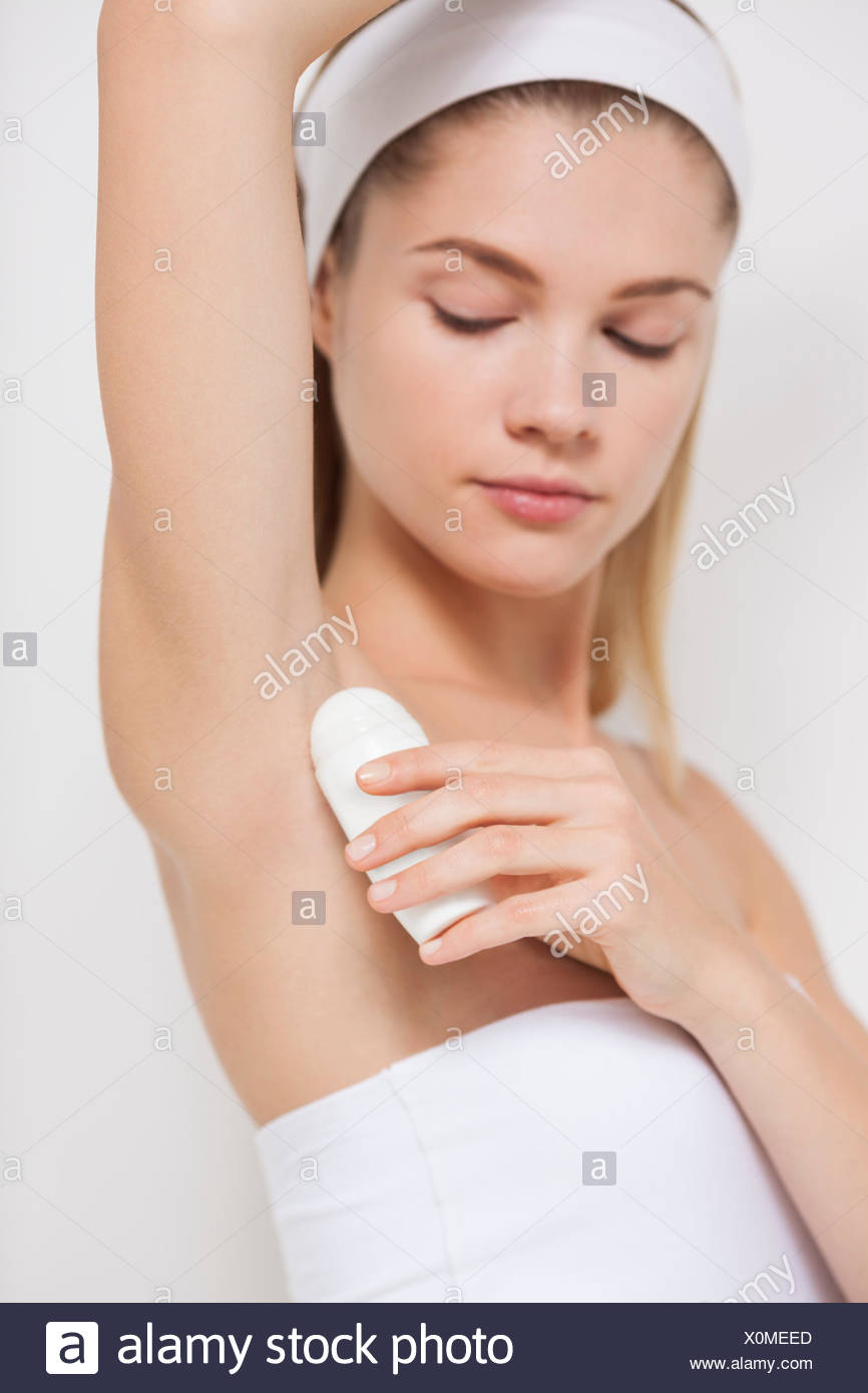 Beautiful woman applying deodorant - Stock Image