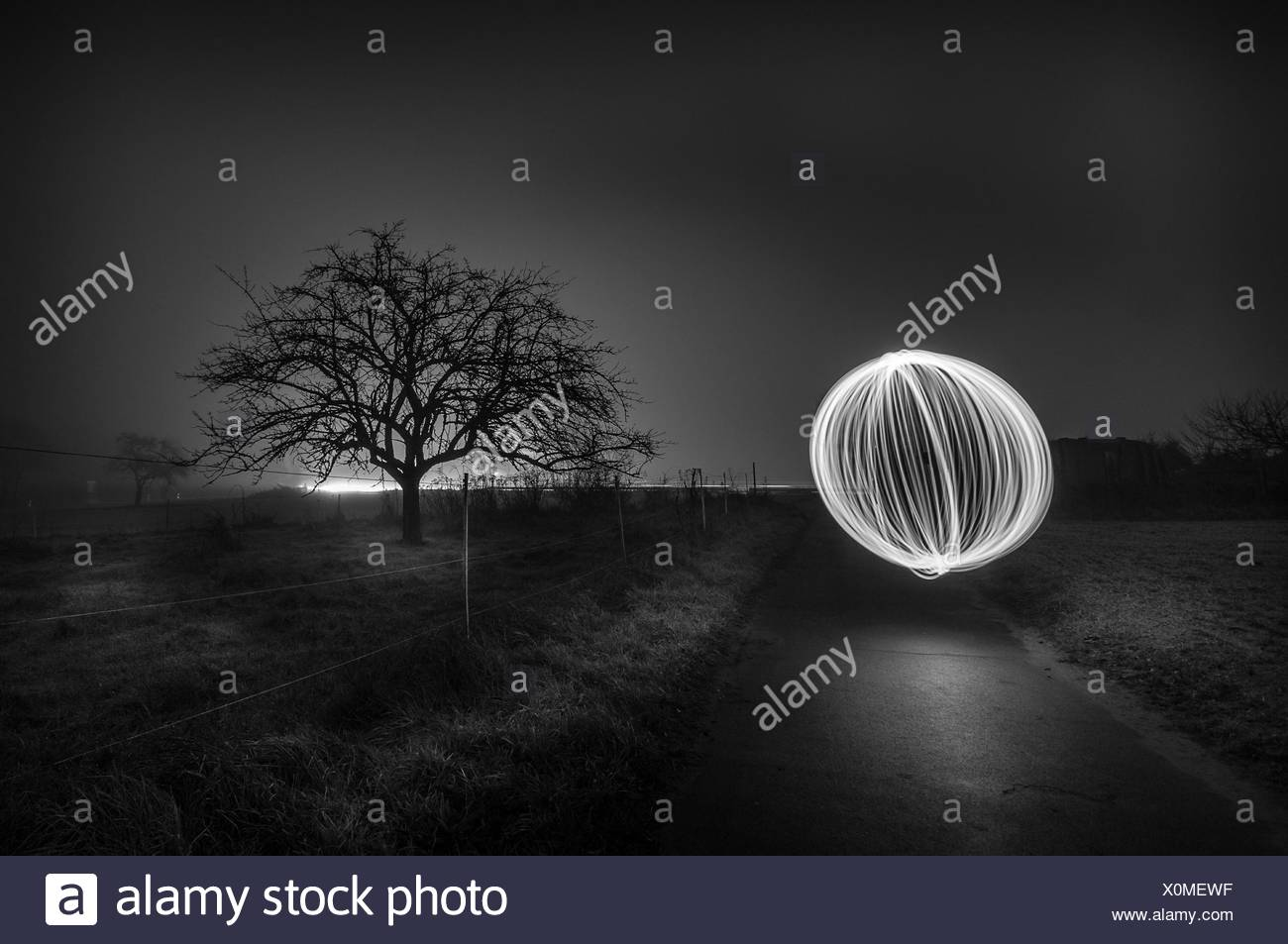 Light Trails Of Wire Wool At Country Road Against Sky At Night - Stock Image