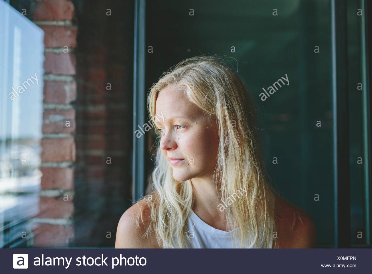Finland, Mid-adult woman looking through window - Stock Image