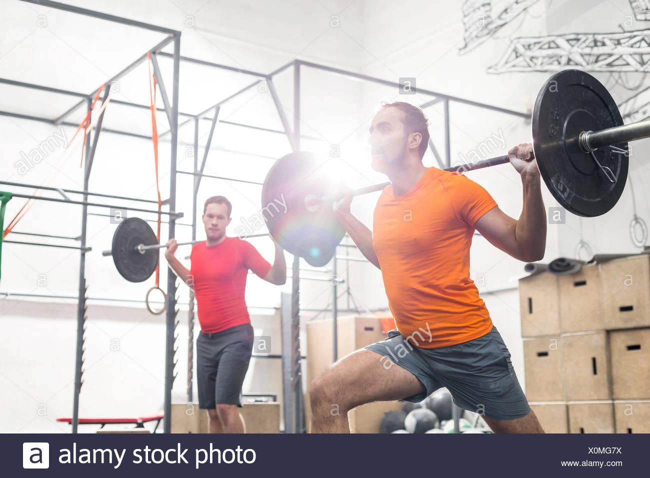 Men lifting barbells in crossfit gym - Stock Image