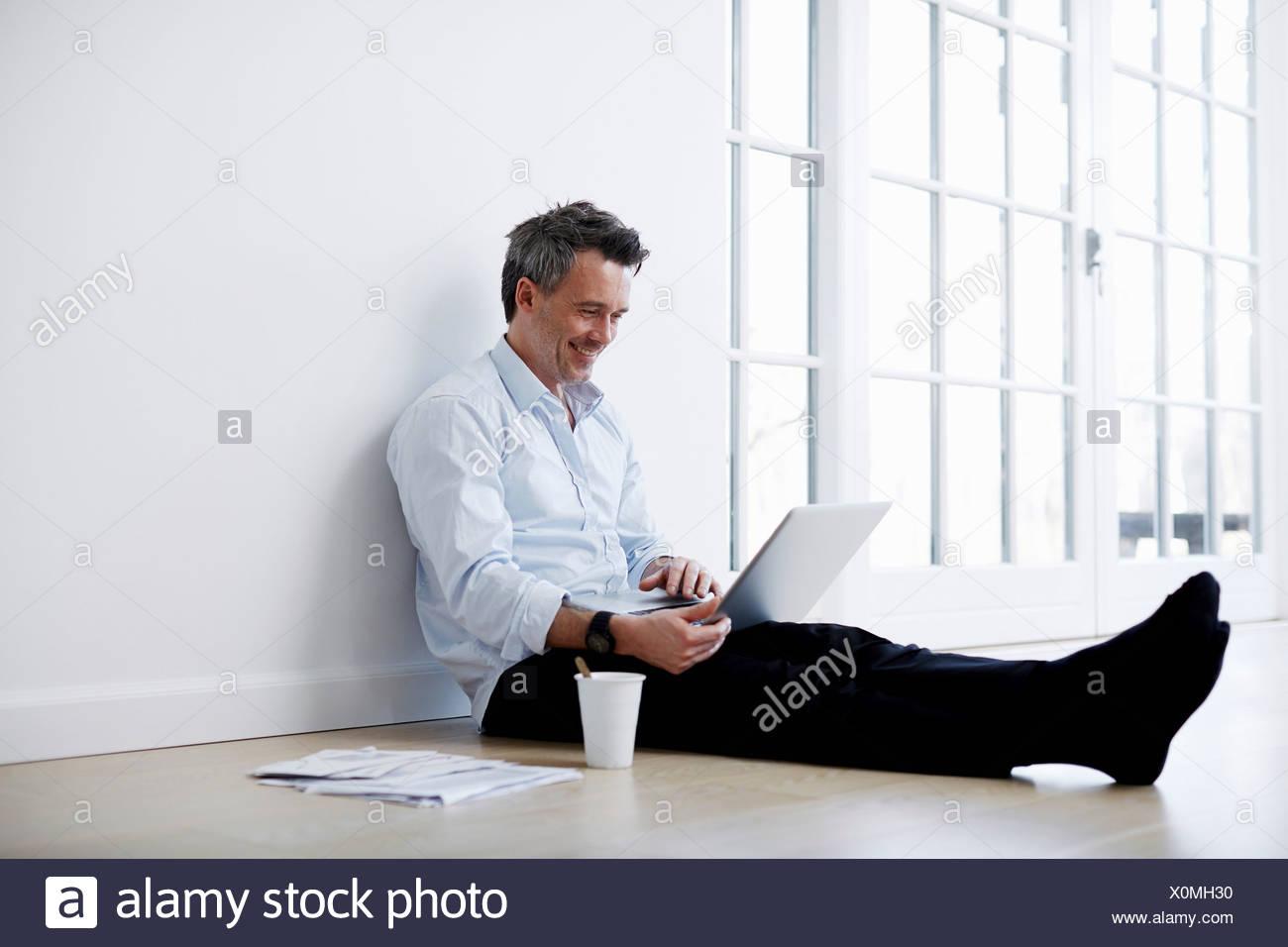 Man sitting on floor sing laptop - Stock Image