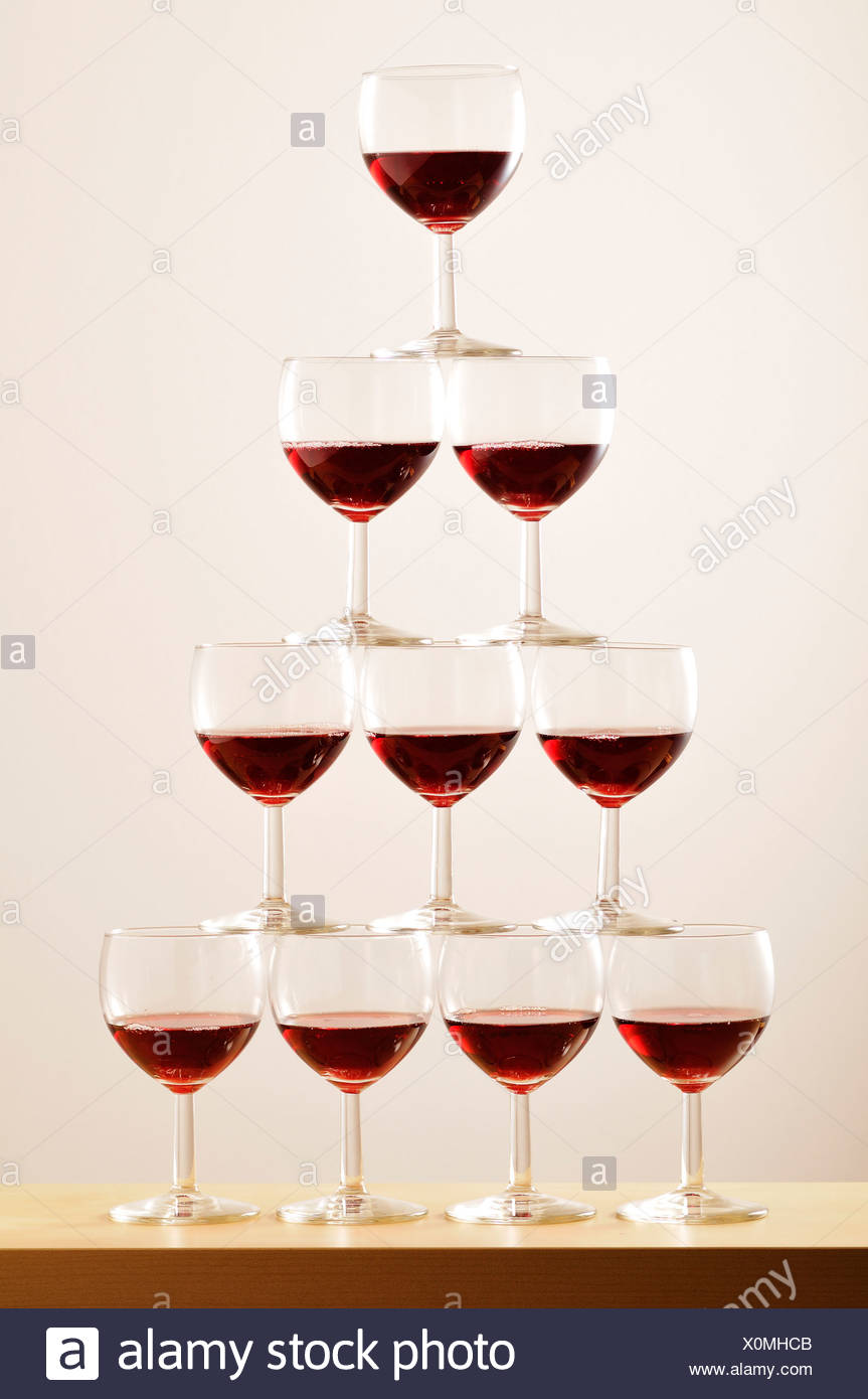 Pyramid of glasses half full of red wine - Stock Image