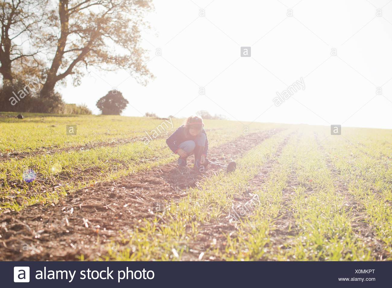 Girl with metal detector crouching and staring down in field - Stock Image