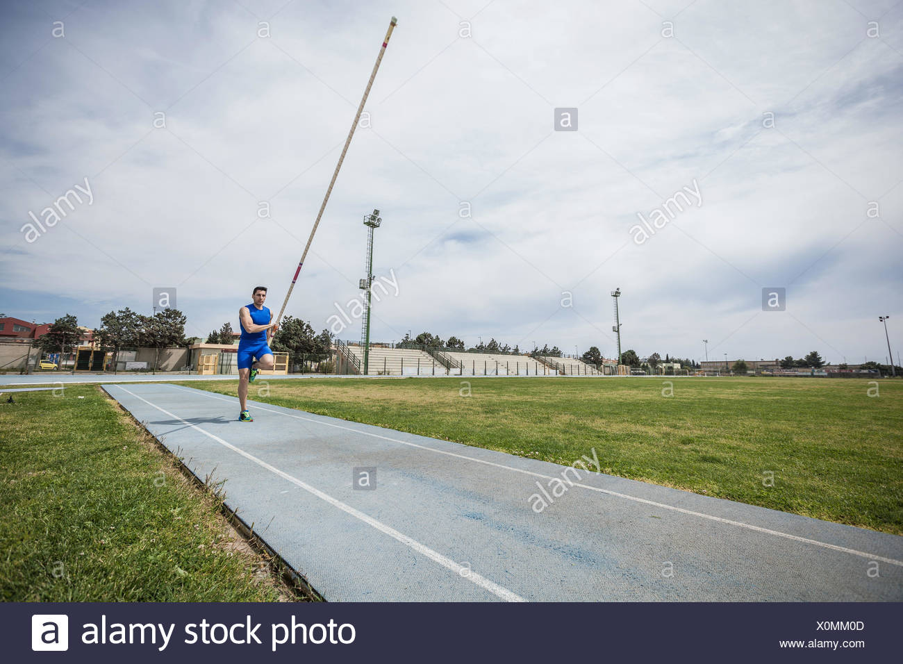 Young male pole vaulter sprinting with pole vault at sport facility - Stock Image