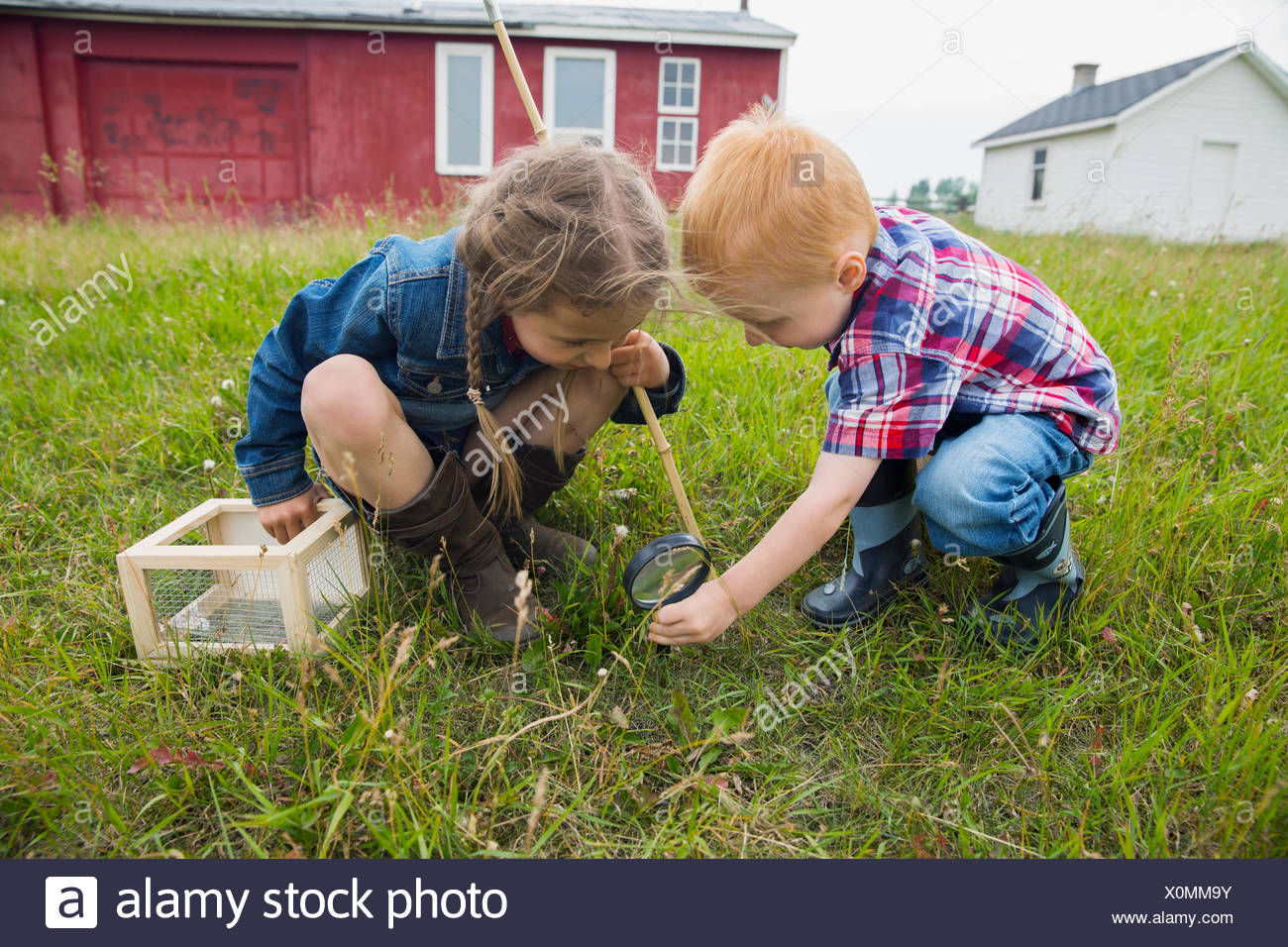 Curious brother and sister with magnifying glass - Stock Image
