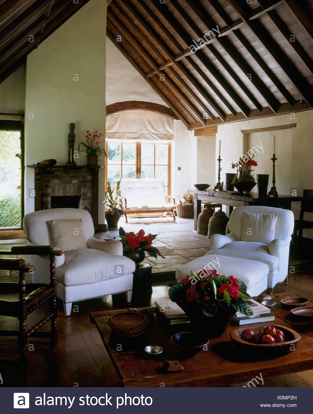 White armchairs and low wooden coffee table in country sitting room with a high, vaulted beamed ceiling Stock Photo