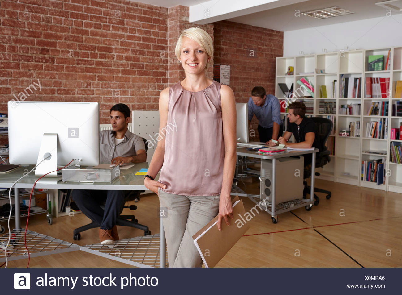 Portrait of mid adult woman in creative office - Stock Image