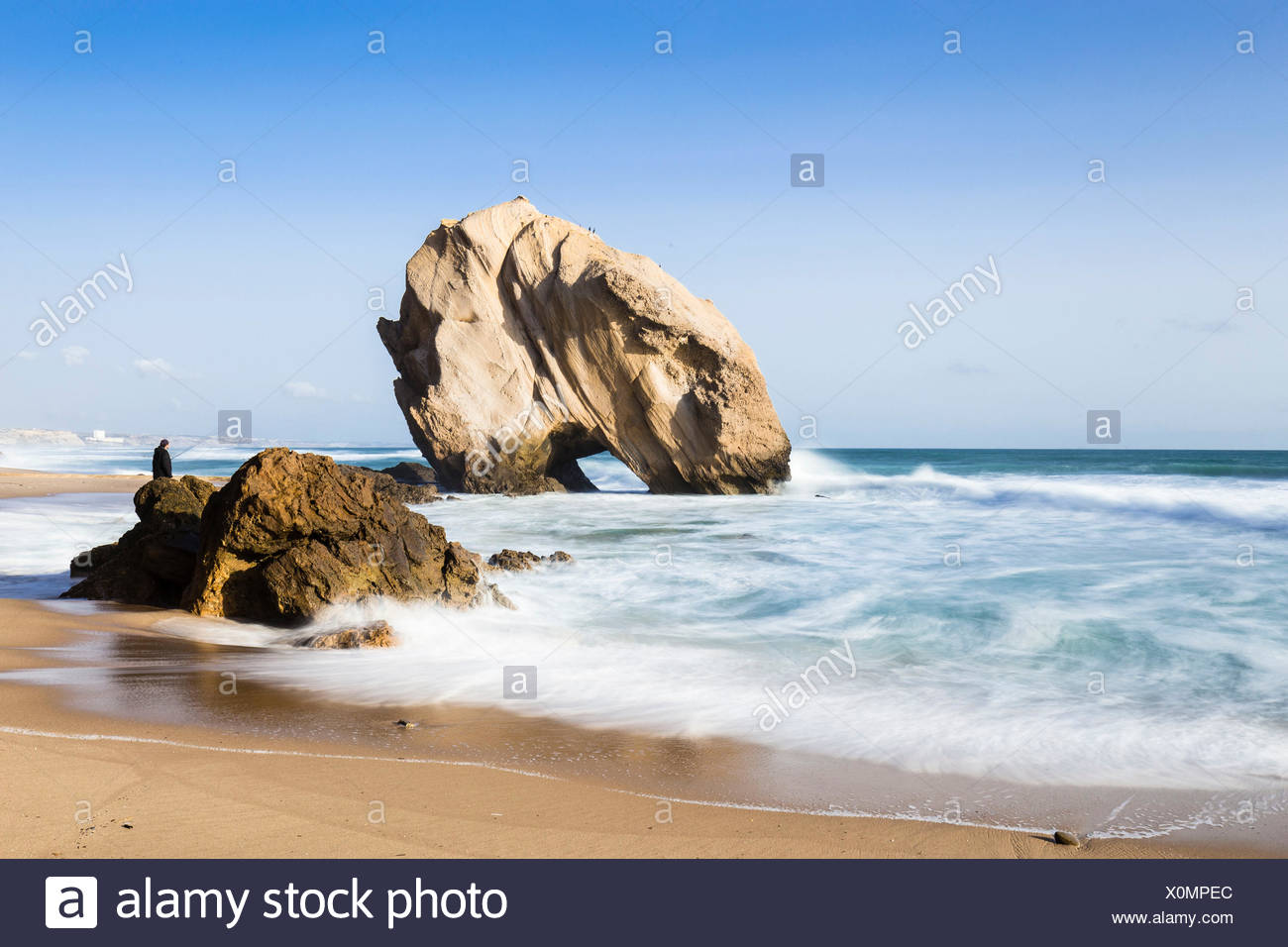 Beach,beach sand,Beauty In Nature,breaking waves,Colour Image,fisherman,Horizon Over Water,Long Exposure,one person,Outdoors,Photography,Portugal,Rock,Rock Formation,Sand,Santa Cruz Beach,Scenics,Sea,Stack,strong currents,Torres Vedras,Tranquil Scene,Trav - Stock Image