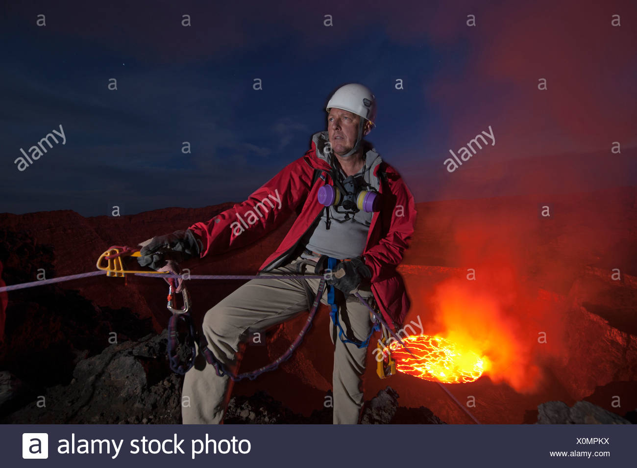 A volcanologist ascends Nyiragongo's crater rim. - Stock Image