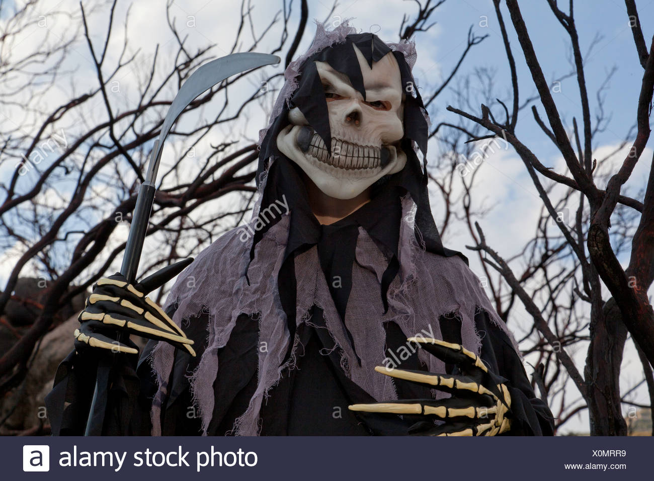 Low angle view of boy dressed up as grim reaper holding spade - Stock Image