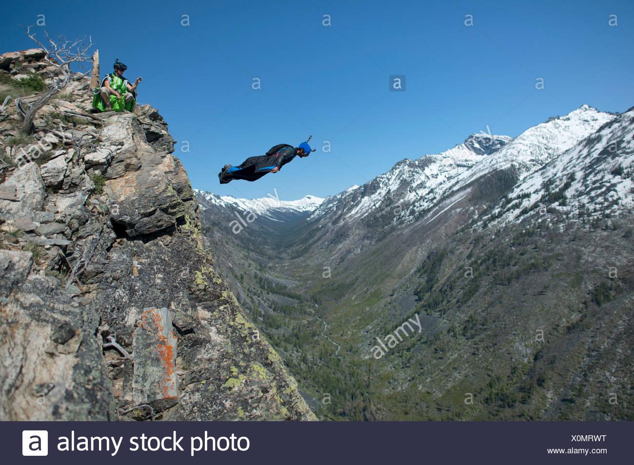 A wingsuit pilot jumps for a mountain proximity flight. - Stock Image