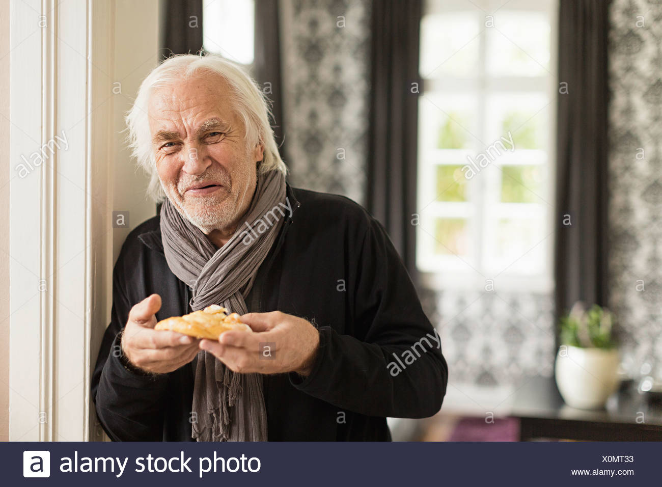 Senior man holding danish pastry - Stock Image