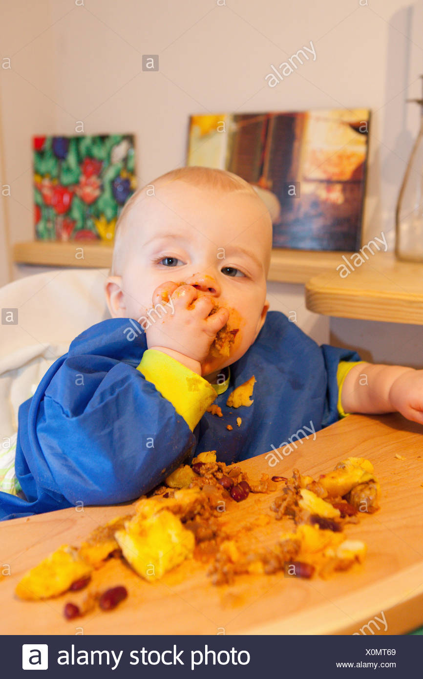 Baby feeding himself - Stock Image