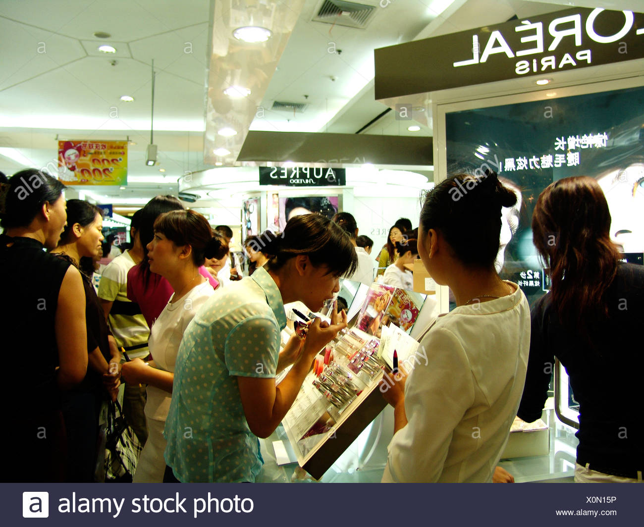Young women try out make up products in cosmetic counter, Xidan shopping area, Beijing, China - Stock Image