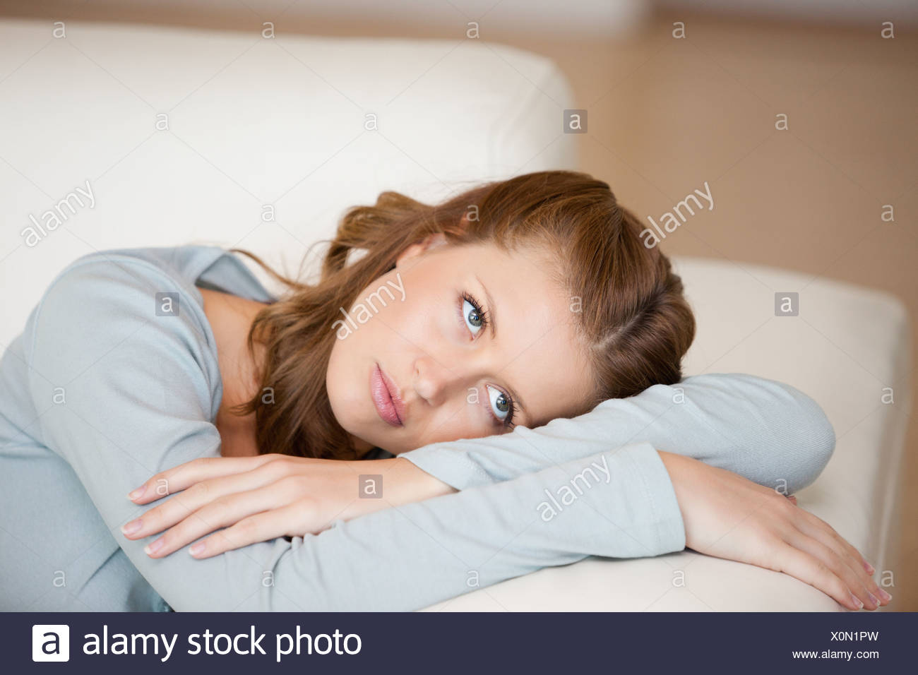 Woman crossing harms while lying on a sofa looking up - Stock Image
