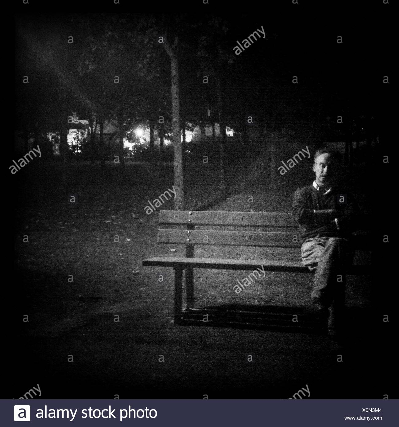 Portrait Of A Man Sitting On Park Bench At Night Stock Photo