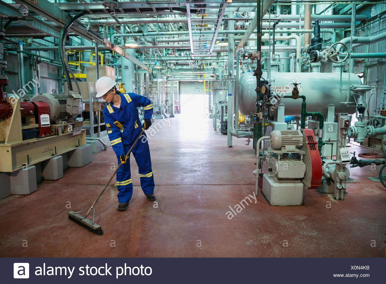 Female worker sweeping floor of gas plant - Stock Image