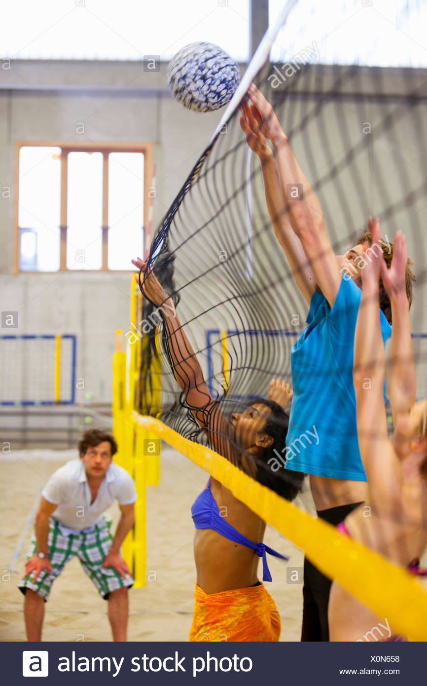 Friends having fun playing indoor beach volleyball - Stock Image