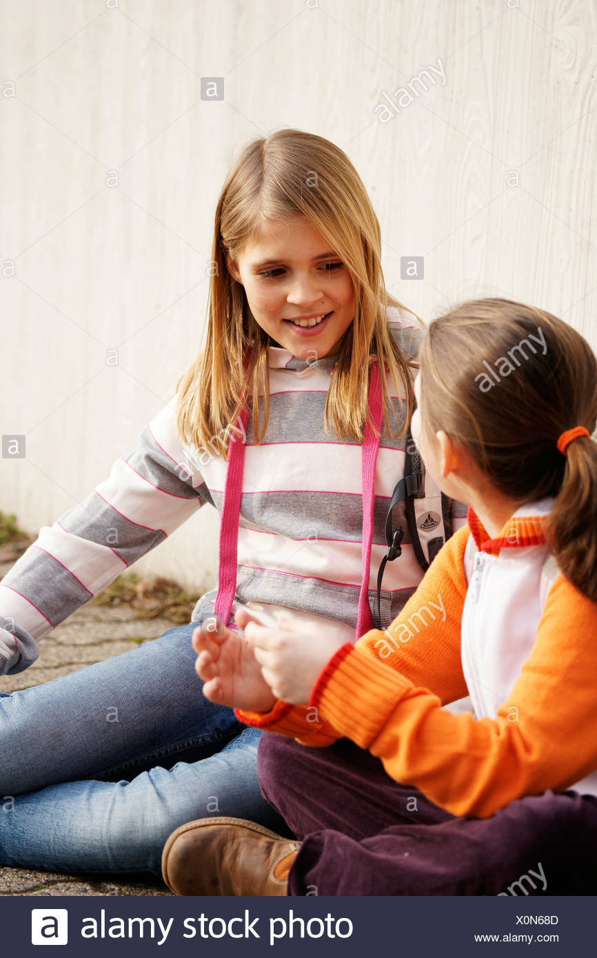 Two girls talking in the schoolyard - Stock Image
