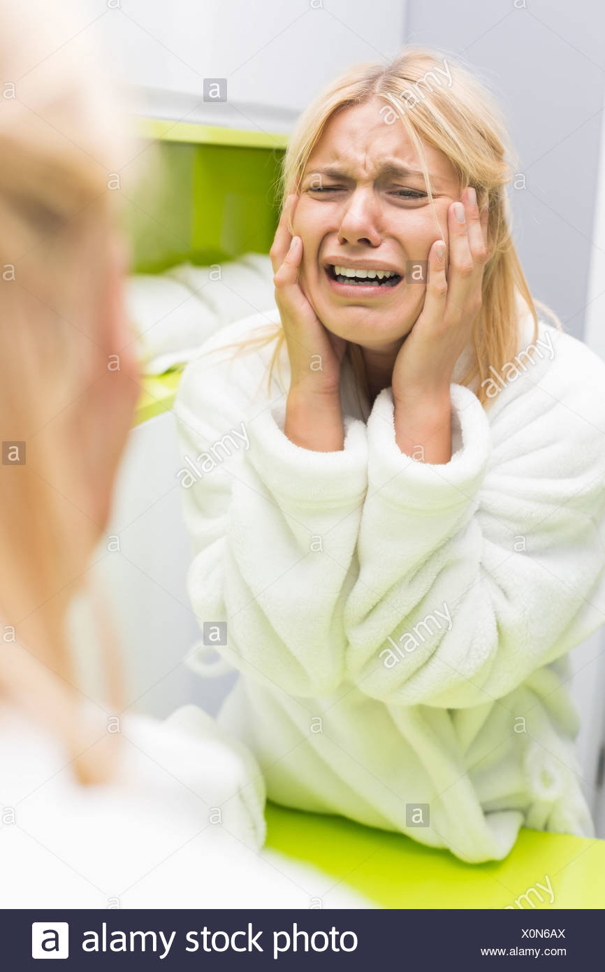 Young ill woman crying while looking at mirrior in bathroom - Stock Image