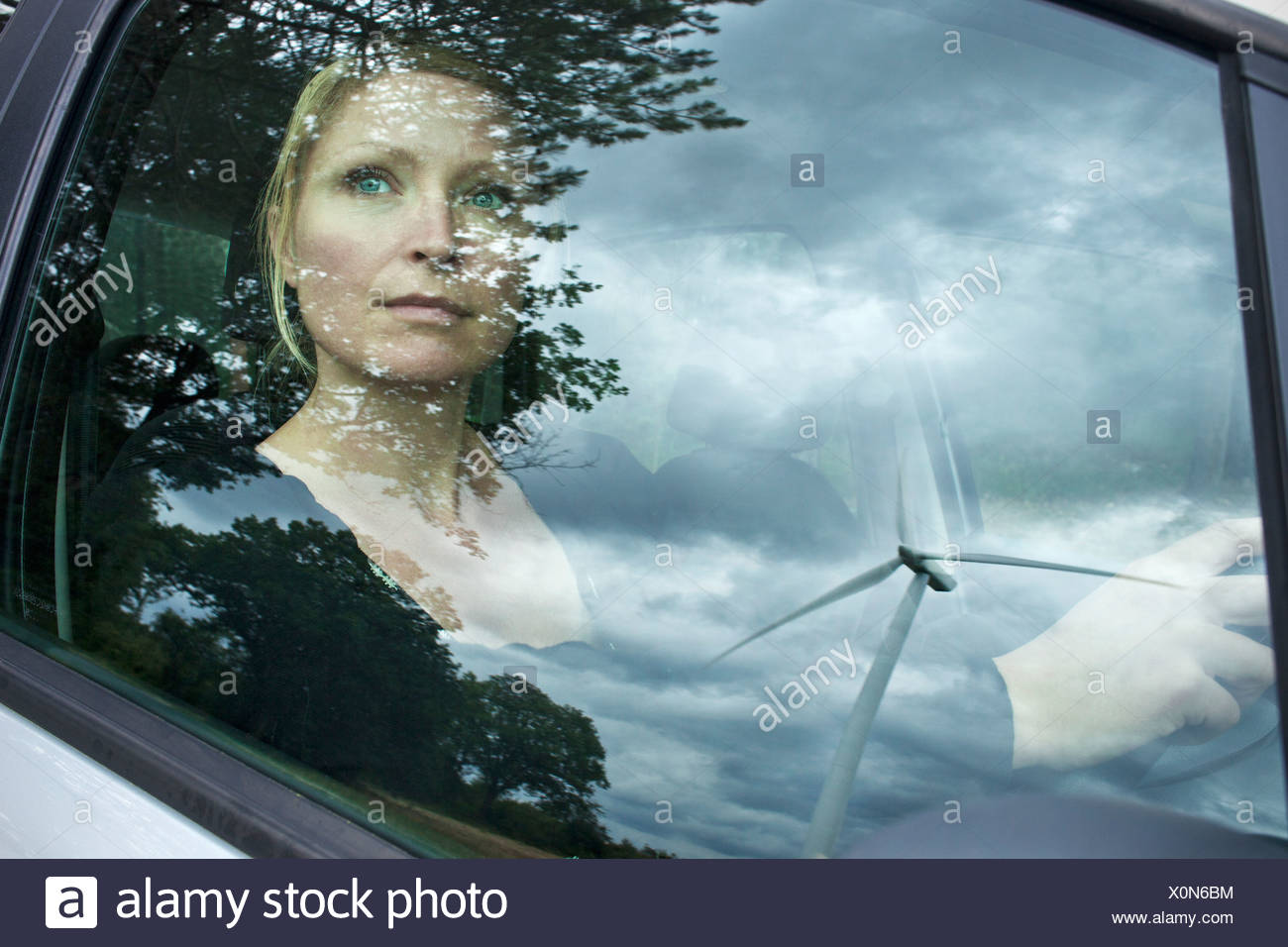 Wind turbine reflected in car window - Stock Image