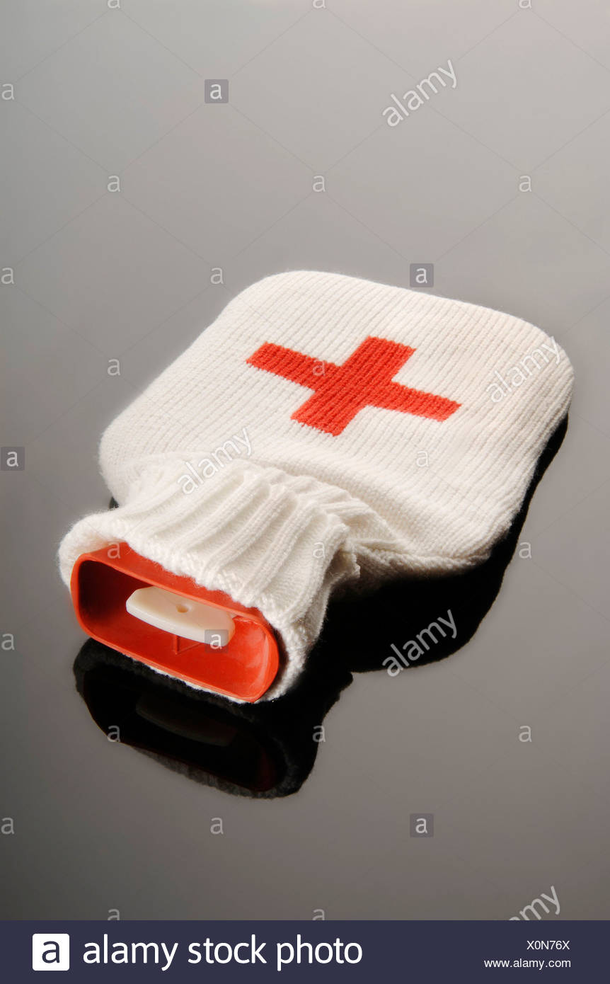 Hot water bottle in a woolen bag with a red cross - Stock Image
