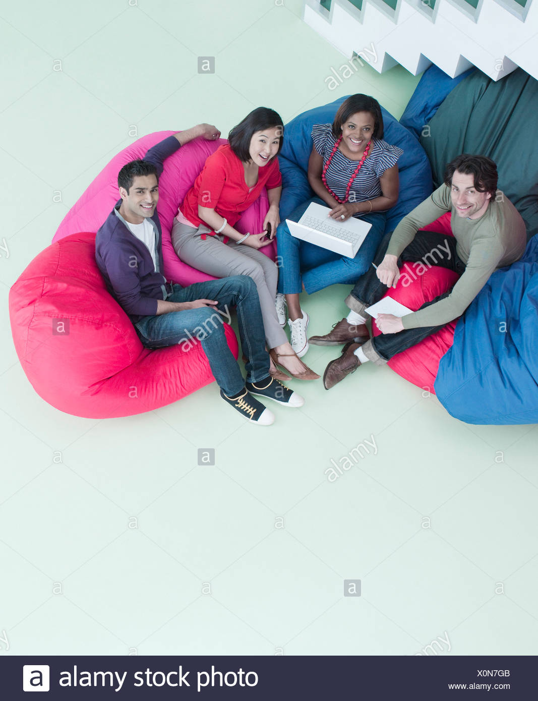 Smiling business people sitting in bean bag chairs - Stock Image