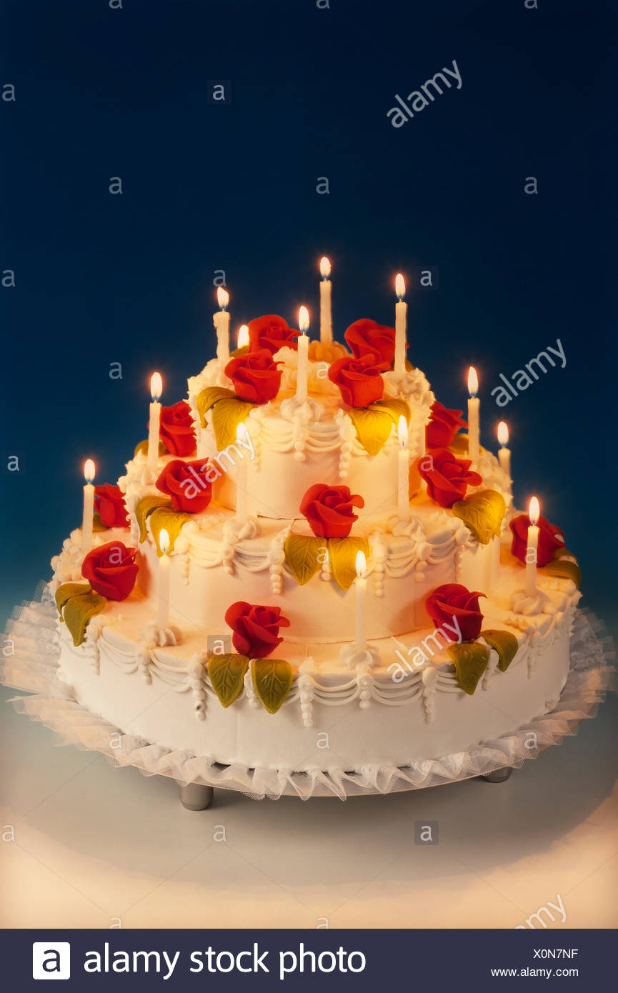 Wedding cake with marzipan roses and lit candles - Stock Image