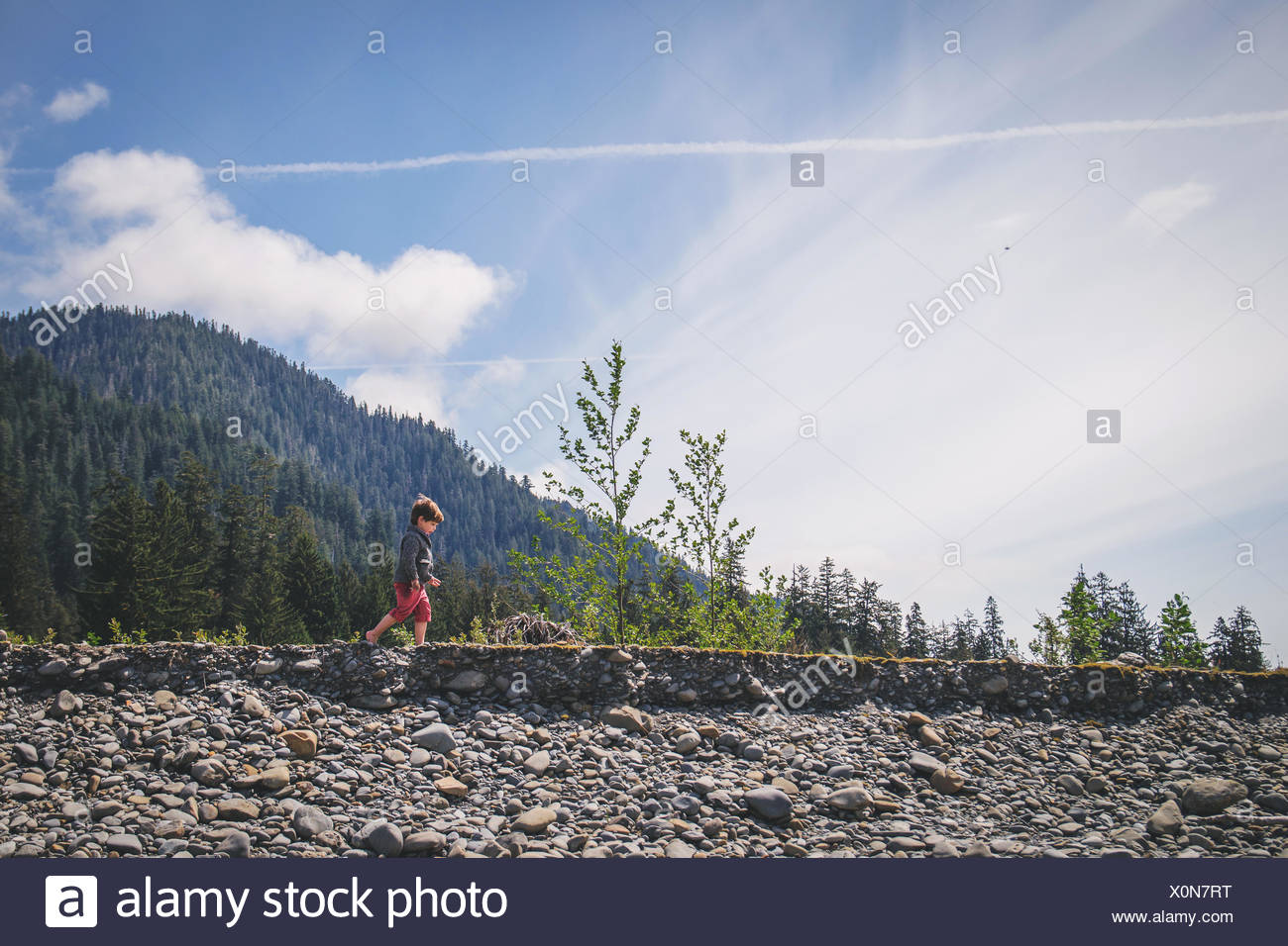 Side view of a boy walking by a stream - Stock Image
