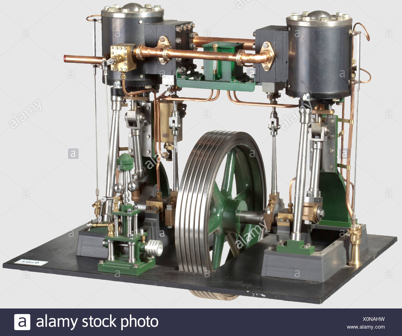 A finely engineered and well presented model twin vertical cylinder stationary engine, Comprising two Stuart No 1 single cylinder engines mounted on a common crankshaft with centrally mounted spoked flywheel with five rope grooves, blued steel clad cylinders 2in bore x 2in stroke, flanged inlet and exhaust pipes, draincocks and pipes, multi-rope driven governor, linkage and valve, mechanical lubricator and pipework, cast beds and metal floor, finished in green, black and polished brightwork. 37 x 40 cm, historic, historical, 20th century, steam engine, steam en, Additional-Rights-Clearences-NA - Stock Image