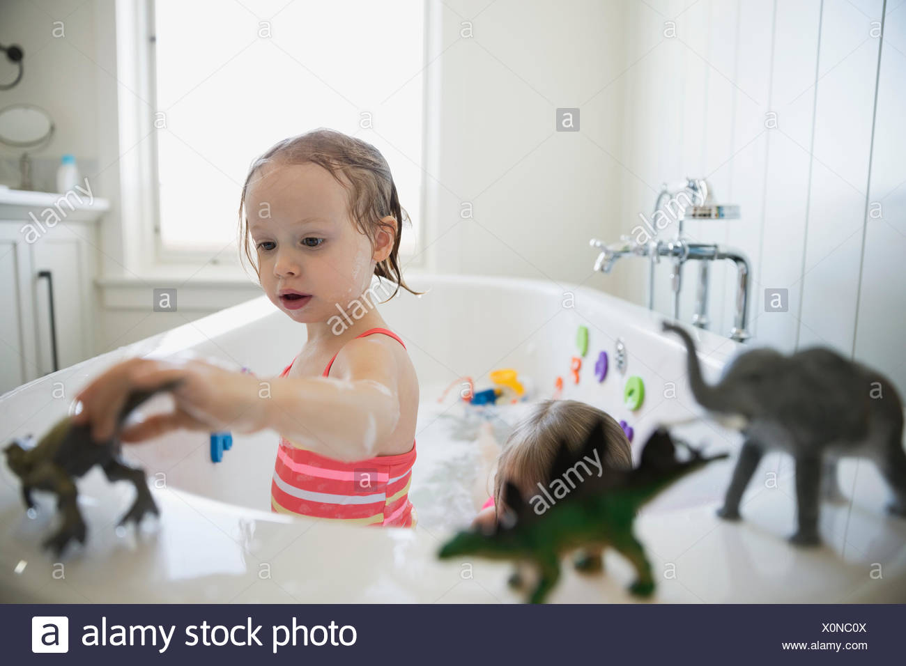 Girl playing with toy dinosaurs in bath - Stock Image