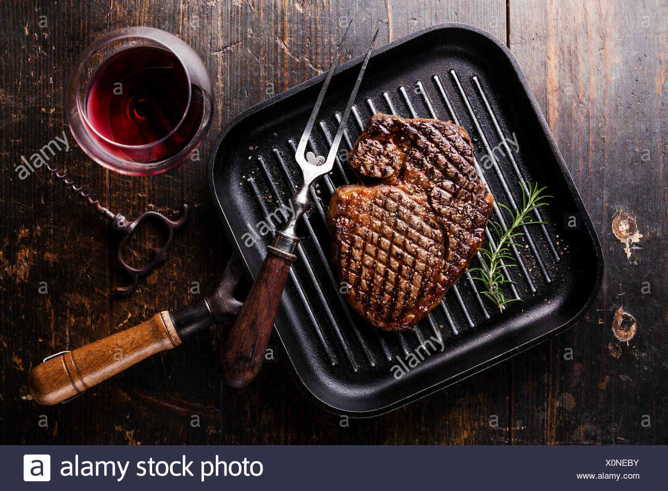 Grilled Black Angus Steak Ribeye on grill iron pan on wooden background with wine Stock Photo