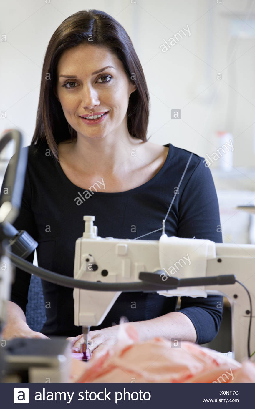 Seamstress using industrial sewing machine - Stock Image