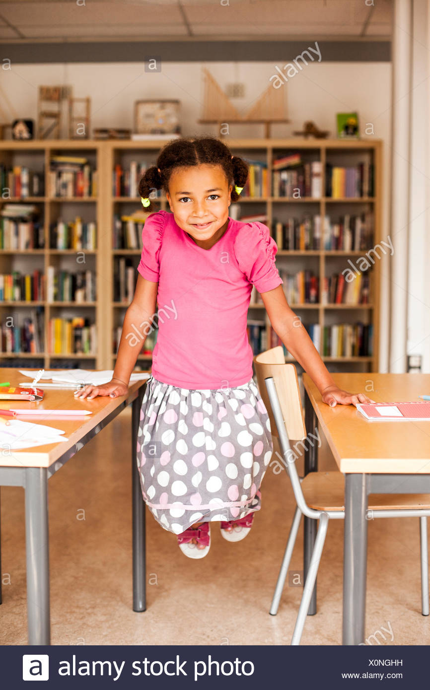 Full length portrait of playful girl in classroom - Stock Image