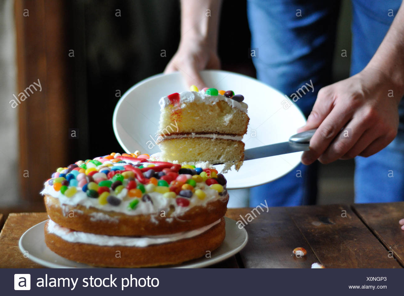 Man cutting a slice of birthday cake - Stock Image