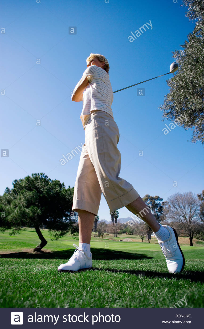Mature woman teeing off with driver on golf course, side view surface level - Stock Image