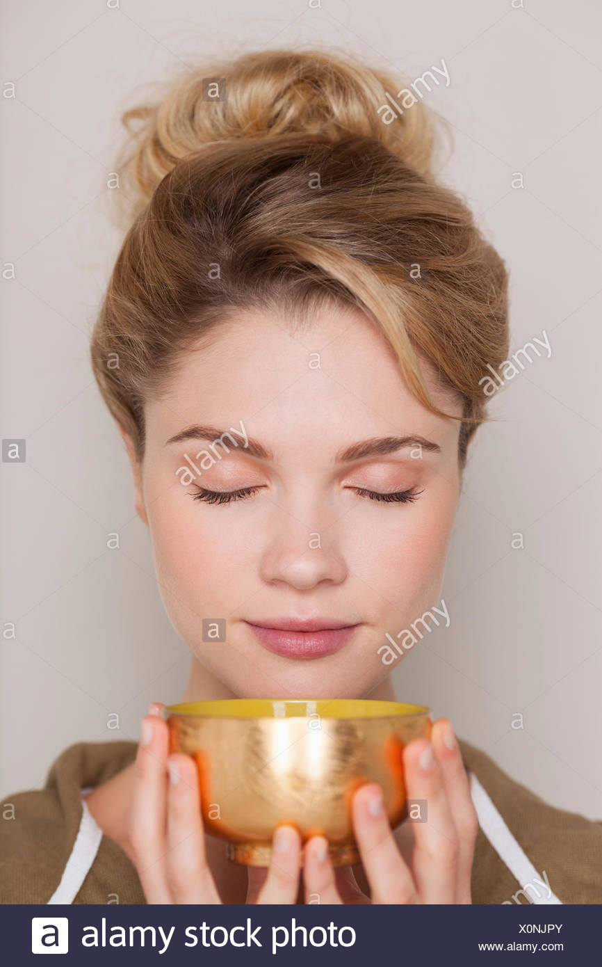 Woman holding a bowl of green tea - Stock Image