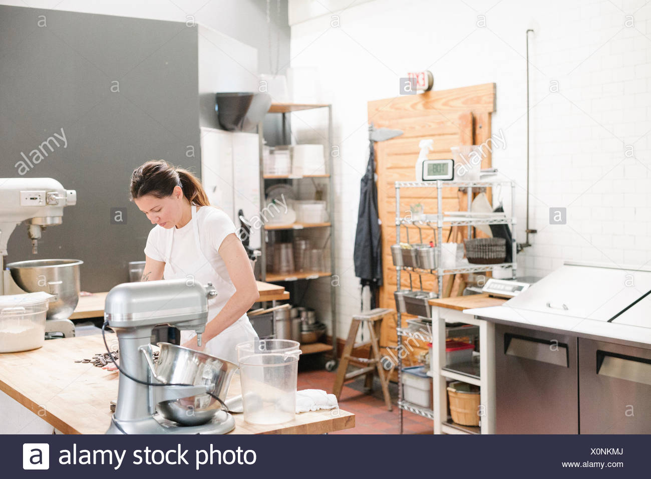 Woman wearing a white apron at a work counter in a bakery. - Stock Image