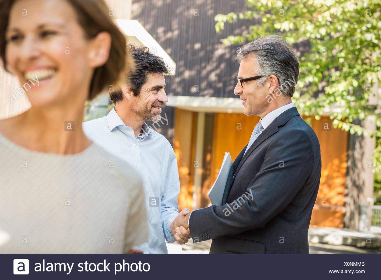 Estate agent and mature man shaking hands outside new house - Stock Image