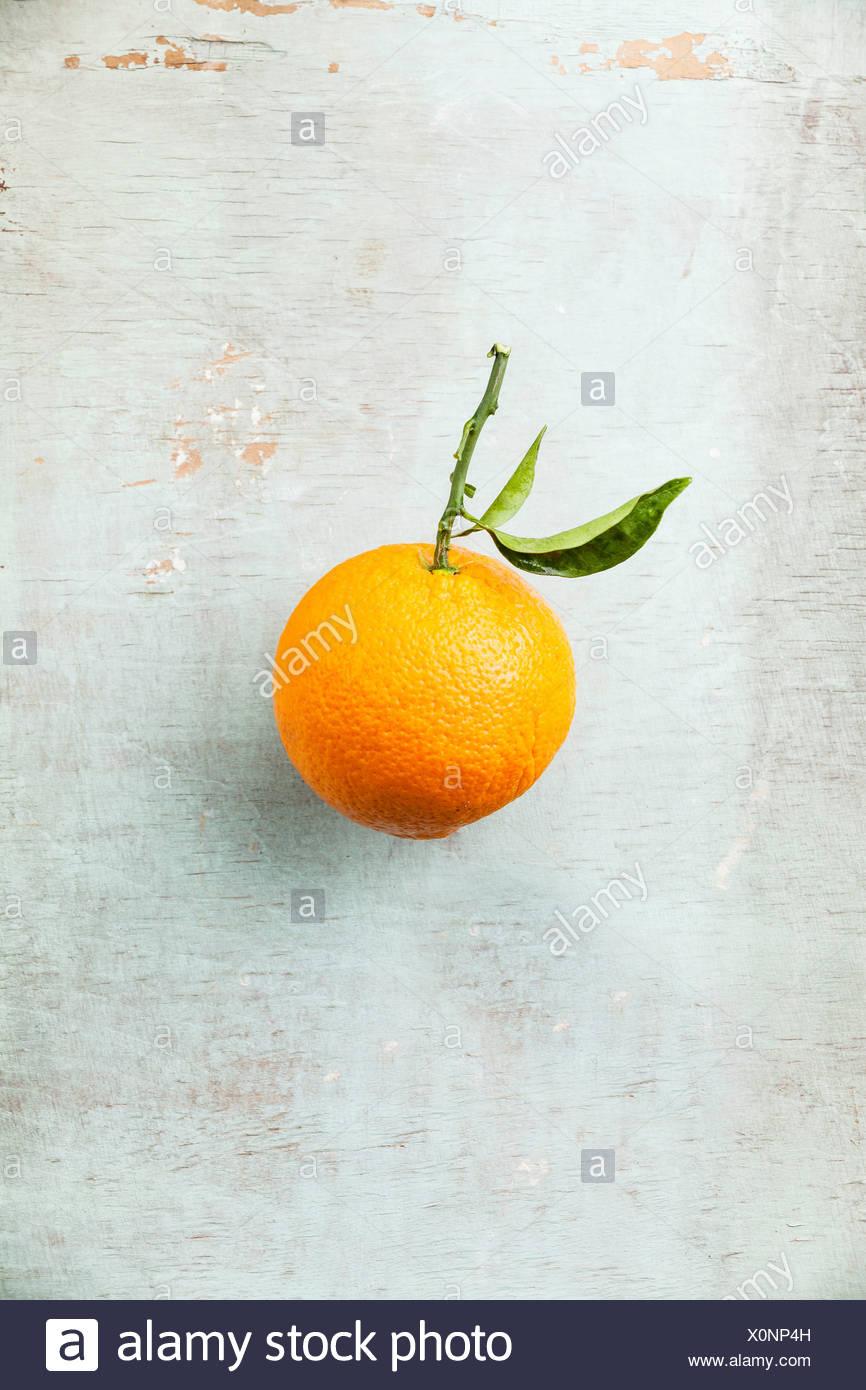 Ripe orange with leaf on textured background - Stock Image