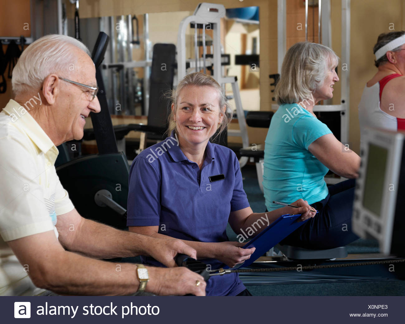 senior male at gym with instructor - Stock Image