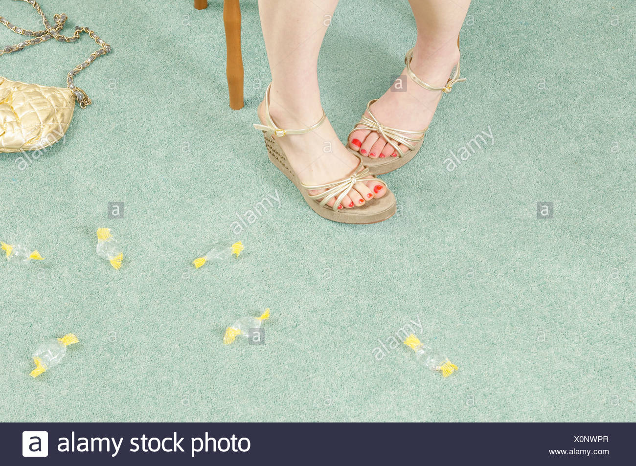 woman's legs with sweet wrappers - Stock Image