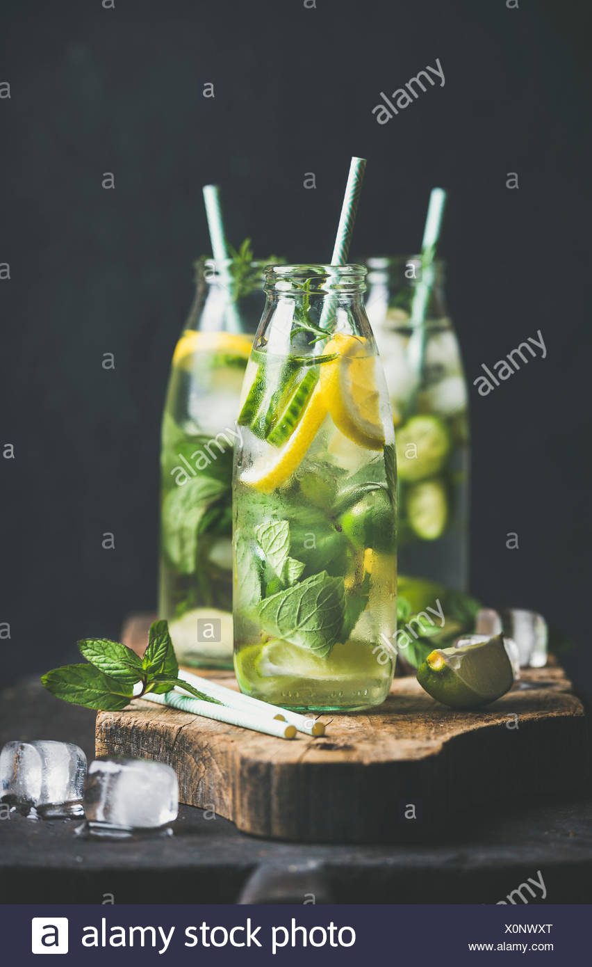 Citrus fruit and herbs infused sassi water for detox, healthy eating or dieting in glass bottles with straws, dark background, selective focus. Clean - Stock Image